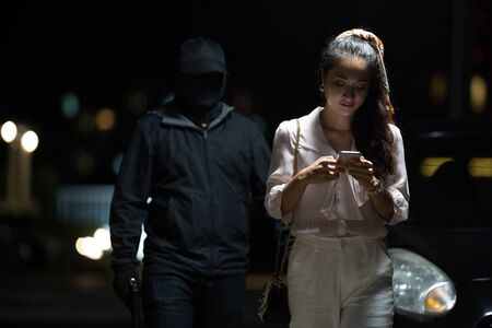 Robber lonely woman she uses the phone in the dark and dangerous
