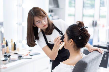 Asian beautician doing makeup for customer. Zdjęcie Seryjne