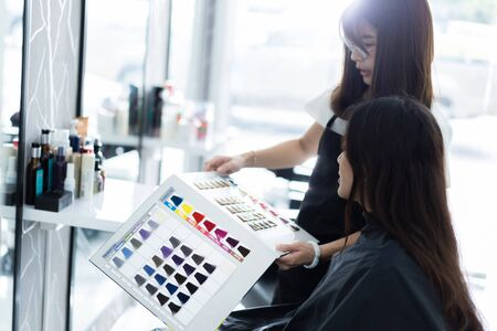 The beautician is giving the customer a choice of color for the hair color.in beauty salon