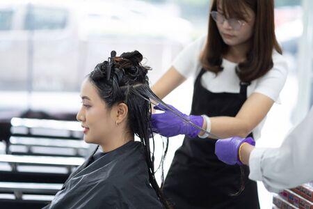 Peluquero asiático teñir el cabello y hacer el cabello para el cliente Foto de archivo