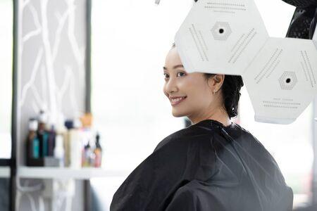 Asian woman dyeing hair in a beauty salon