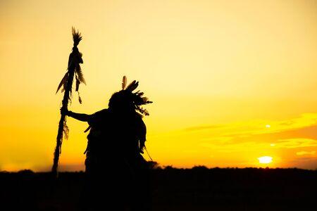 Die Indianer reiten auf einem einsatzbereiten Pferd und Speer Im Lichte der Silhouette Standard-Bild