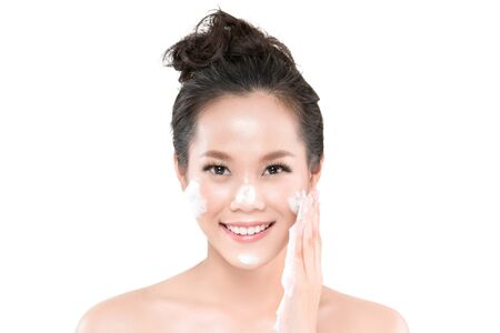 Asian woman going to use a facial foam to wash cosmetics off the face on white background