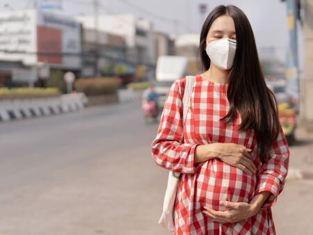 Asian pregnant woman she is in the middle of the road wear a PM2.5 dust mask. 写真素材