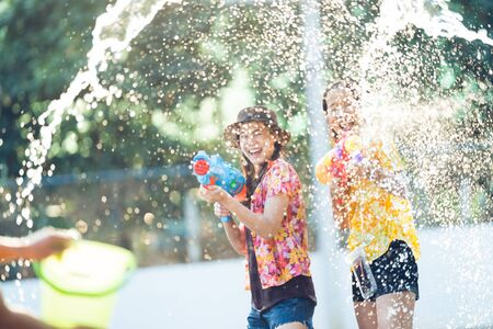 Asian people are using water guns play songkran festival in the summer april