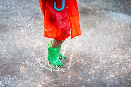 Asian girl is wearing green shoes. She jumps and is raining. Reklamní fotografie