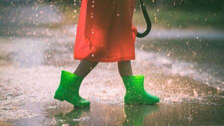 Asian girl is wearing green boot. She is in the rain. Reklamní fotografie