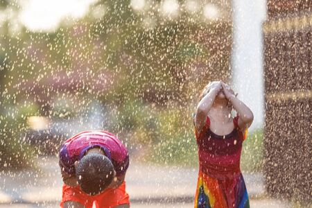 Asian children playing in the rain are happy. Reklamní fotografie