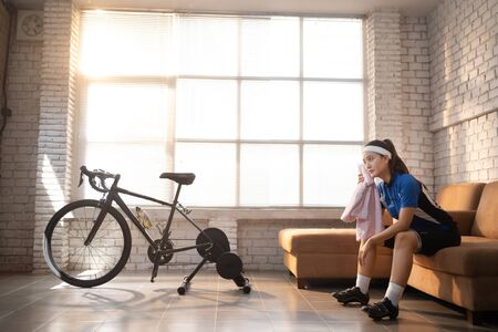 Asian woman cyclist. She is exercising in the house. By cycling on the trainer And playing online bike games, she breaks