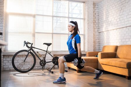 Cyclist exercise with Leg lunges. She's at home.