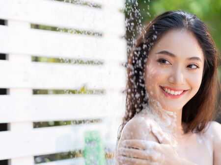 Asian woman, she uses a shower and wash hair outside. She is resting at the resort