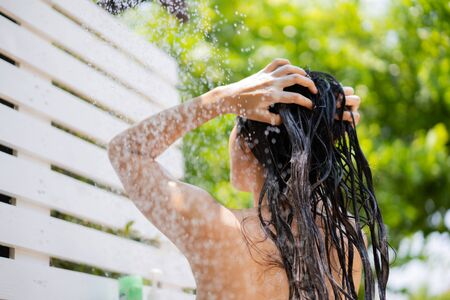 Asian woman, she uses a shower and wash hair outside. She is resting at the resort.focus on the shoulder