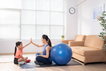 Asian mother and daughter Exercising at home They are having fun together 스톡 콘텐츠