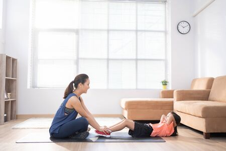 Mother and daughter exercising at home They're doing sit-ups.