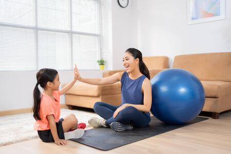 Mother and daughter exercise at home