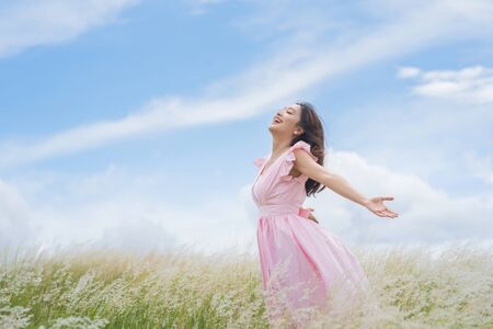 Beautiful asian woman She is having freedom at the meadow. She is happy.