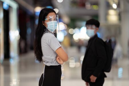 Asian woman wear a virus protection mask. In the mall Stock Photo