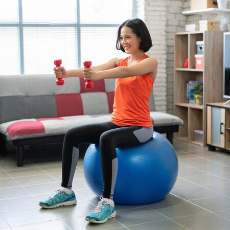 Beautiful asian woman Use dumbbell exercises at home She is sitting on the ball