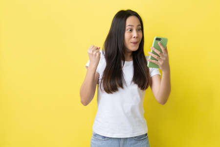 Beautiful Asian woman. She feels shocked with the phone on a yellow background.