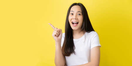Asian woman She pointed to the empty side on the yellow background. Stock Photo