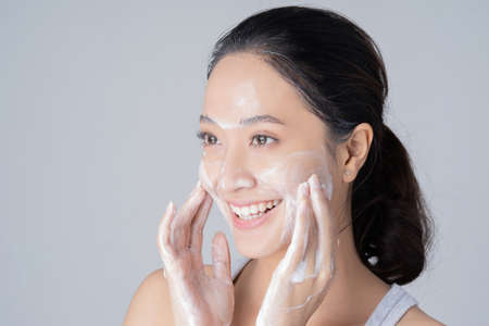 Beautiful female asian Wash face with cleansing foam. in studio Imagens
