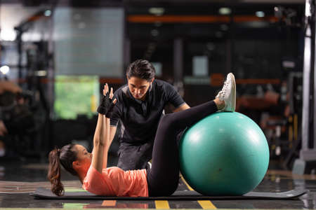 personal trainer is teaching abdominal exercises with a ball, they are in the gym. Stock Photo