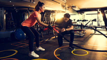personal trainer timing for asian women she exercises with a rope. Stock Photo