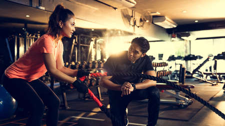 Personal trainer timing for asian women she exercises with a rope.