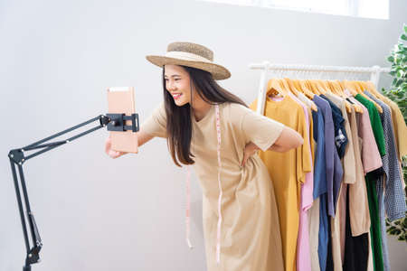 Asian woman selling vintage clothes, she is live on social media.She is answering customers questions. 版權商用圖片 - 155120576
