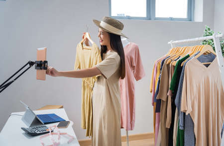 Asian woman selling vintage clothes, she is live on social media.She is answering customers questions. 版權商用圖片 - 155120424