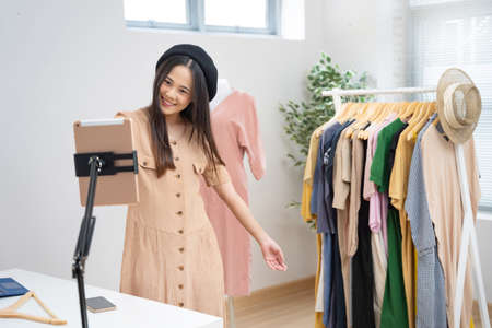 Asian woman selling vintage clothes, she is live on social media. 版權商用圖片
