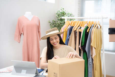 Asian woman selling vintage clothes, she is live on social media.She packs a box