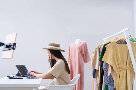 Asian woman selling vintage clothes, she is live on social media.She is answering customers questions.