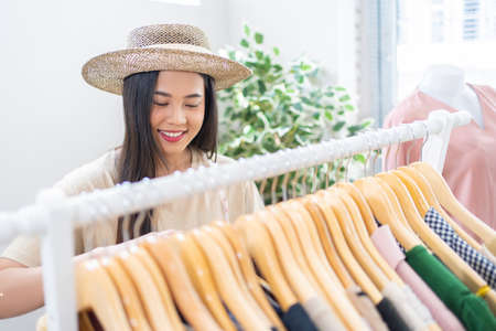 Asian woman is preparing a shir selling vintage clothes, she is live on social media. 版權商用圖片 - 155120995