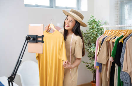 Asian woman selling vintage clothes, she is live on social media. 版權商用圖片 - 155120904
