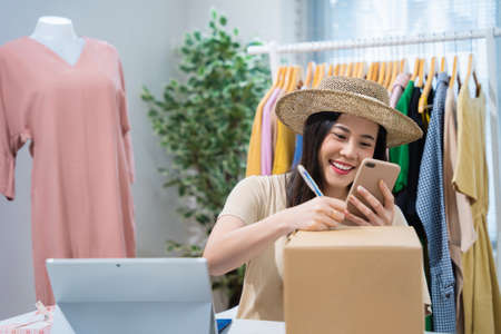 Asian woman selling vintage clothes, she is live on social media.She packs a box 版權商用圖片 - 156455560