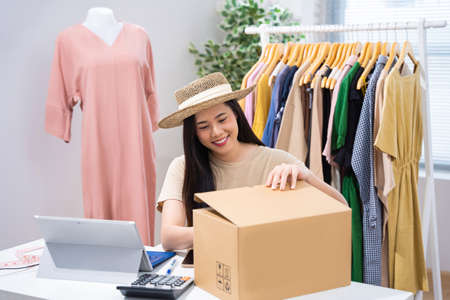 Asian woman selling vintage clothes, she is live on social media.She packs a box 版權商用圖片 - 155121271