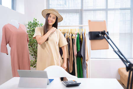 Asian woman selling vintage clothes, she is live on social media.She is measuring the shirt size.