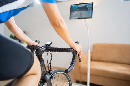Asian woman cyclist. She is exercising in the house.By cycling on the trainer and play online bike games 版權商用圖片 - 156115958