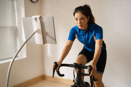Asian woman cyclist. She is exercising in the home.By cycling on the trainer and play online bike games. 版權商用圖片 - 156115996
