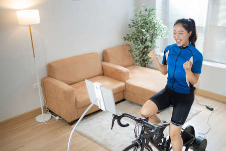 Asian woman cyclist. She is exercising in the home.By cycling on the trainer and play online bike games.She is glad 版權商用圖片 - 156115999