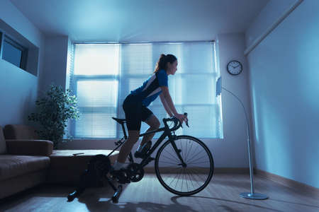 Asian woman cyclist. She is exercising in the home.By cycling on the trainer and play online bike games.She stood up spinning 版權商用圖片 - 156116005