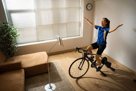 Asian woman cyclist. She is exercising in the home.By cycling on the trainer and play online bike games.She is glad 版權商用圖片