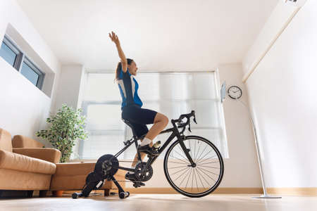 Asian woman cyclist. She is exercising in the home.By cycling on the trainer and play online bike games.She is