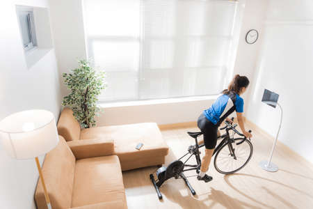 Asian woman cyclist. She is exercising in the home.By cycling on the trainer and play online bike games.