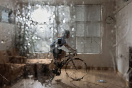 Asian woman cyclist. She is exercising in the home.By cycling on the trainer and play online bike games.During the rainy season