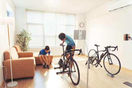Asian couple. They are preparing bikes on the trainer and play online bike games. 版權商用圖片 - 156116046