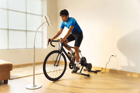 Asian man cyclist. he is exercising in the house.By cycling on the trainer and play online bike games 版權商用圖片 - 156116213