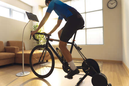 Asian man cyclist. he is exercising in the house.By cycling on the trainer and play online bike games 版權商用圖片 - 156116215