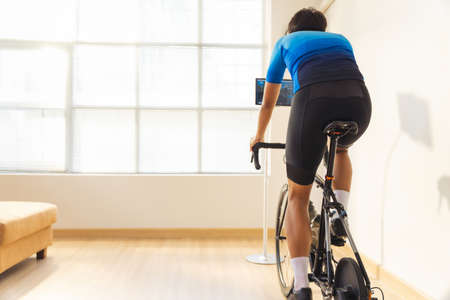Asian man cyclist. he is exercising in the house.By cycling on the trainer and play online bike games 版權商用圖片 - 156116224